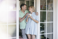 Happy mature couple standing at French window - JOSF02465