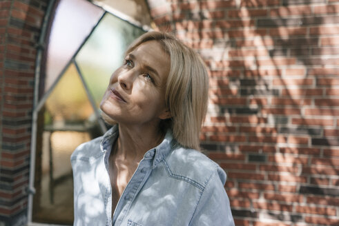 Portrait of mature woman in front of brick wall looking up - JOSF02471