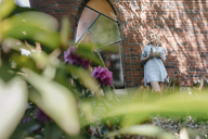 Relaxed mature woman leaning at house wall in garden - JOSF02474