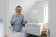 Mature woman with cell phone and toothbrush in bathroom - JOSF02489