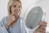 Mature woman looking in beauty mirror in bathroom checking her teeth - JOSF02492