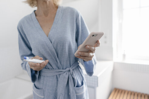 Close-up of woman with cell phone and toothbrush in bathroom - JOSF02495