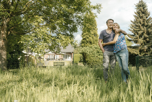 Smiling mature couple embracing in garden of their home - JOSF02498