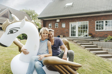 Portrait of smiling mature couple sitting on inflatable pool toy in garden of their home - JOSF02504