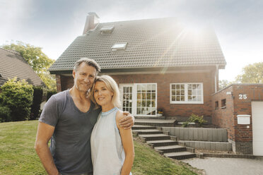Portrait of smiling mature couple embracing in garden of their home - JOSF02507