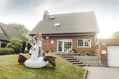 Portrait of smiling mature couple with inflatable pool toy in garden of their home - JOSF02510