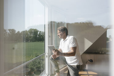 Mature man using tablet at the window - JOSF02516