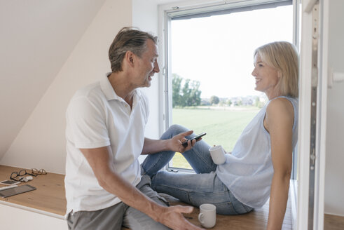 Mature couple with cell phone sitting at the window - JOSF02519