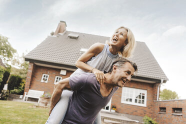 Happy mature couple in garden of their home - JOSF02528