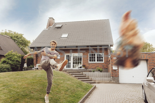 Mature man kicking away garden gnome in front of his home - JOSF02534