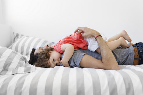 Man wearing grey T-shirt and jeans lying on bed with stripy duvet, hugging baby girl in red dress. - MINF04480