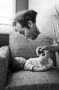 Man leaning over newborn baby girl lying on armchair. - MINF04501