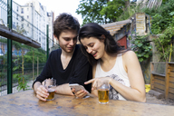 Young couple at an outdoor bar with beer and cell phone - AFVF01228
