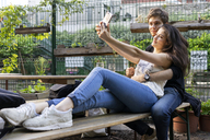 Young couple taking a selfie at an outdoor bar - AFVF01231