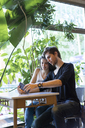 Young couple sitting at table using cell phone - AFVF01237
