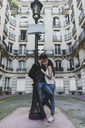 France, Paris, young couple in love standing at street lantern in front of urban building - AFVF01240