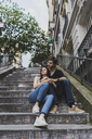 France, Paris, young couple sitting on stairs in the district Montmartre - AFVF01243