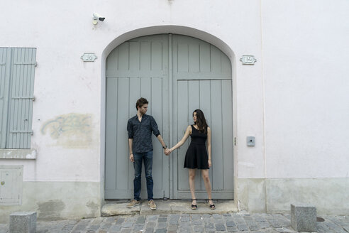 Young couple standing hand in hand in front of building - AFVF01261