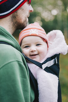 A baby in a sling being carried by her father, outdoors in winter. - MINF04827
