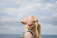 A young girl raising her face to the sun. - MINF04875