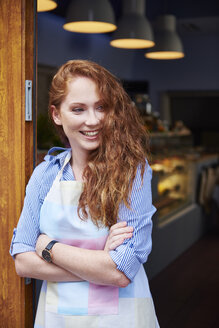 Happy young woman at the entrance of a bakery - ABIF00801