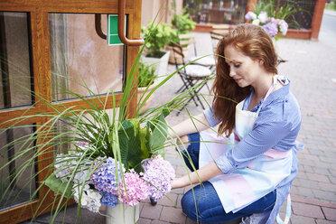 Young woman opening the door of a shop with flowers - ABIF00804