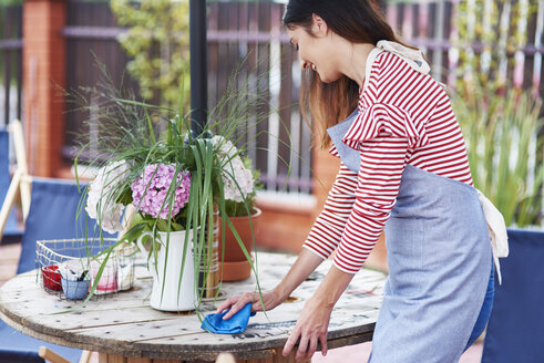 Woman cleaning the table at a cafe - ABIF00810