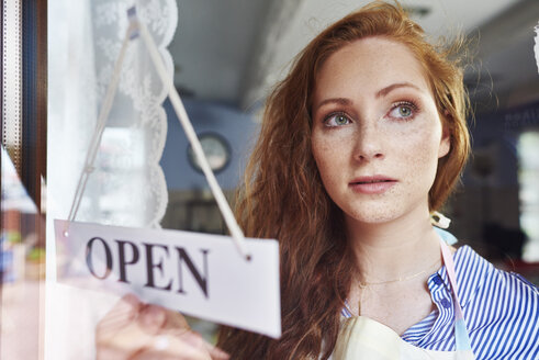Young woman opening a shop - ABIF00813