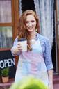 Portrait of smiling waitress offering a coffee - ABIF00816