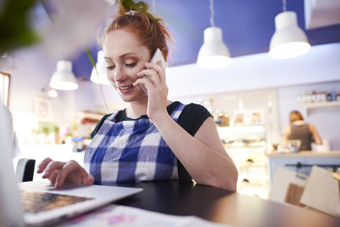 Smiling young woman working in a cafe using laptop and cell phone - ABIF00825