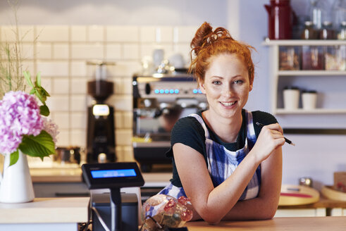 Portrait of smiling young woman at the counter in a cafe - ABIF00828
