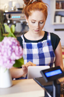 Young woman working in a cafe using tablet - ABIF00831