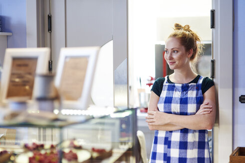 Smiling young woman in a cafe looking sideways - ABIF00834