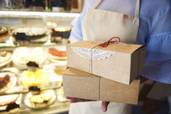 Close-up of woman holding cake boxes in a confectionery shop - ABIF00837