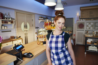 Portrait of smiling young woman at the counter in a cafe - ABIF00843