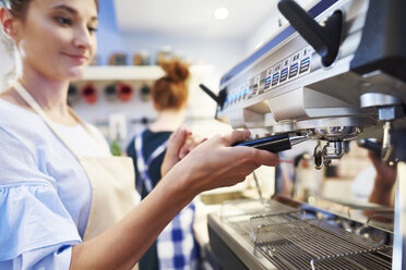 Female barista making coffee at a cafe - ABIF00846