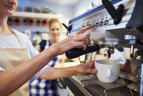 Female barista making coffee at a cafe - ABIF00849