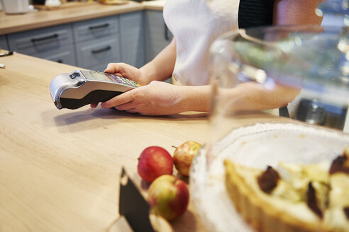 Waitress holding card reader at counter in a cafe - ABIF00852