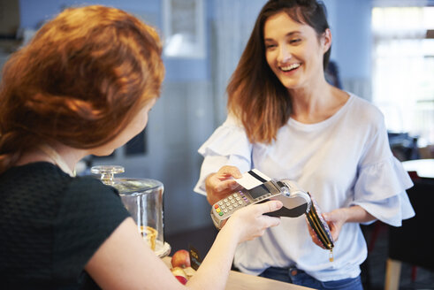 Happy customer paying by credit card in a cafe - ABIF00858