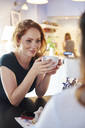 Smiling young woman drinking coffee with friend at cafe - ABIF00864