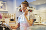 Smiling woman working in a cafe talking on cell phone - ABIF00867