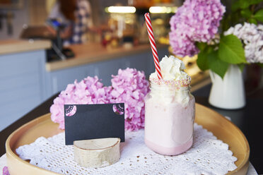 Glass of strawberry milkshake with whipped cream on tray in a cafe - ABIF00870