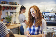 Smiling waitress talking to customer at counter in a cafe - ABIF00873