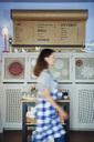 Waitress walking past drinks menu in a cafe - ABIF00879