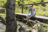 Mother and daughter sitting on wooden bridge, mountain stream - DIGF04724