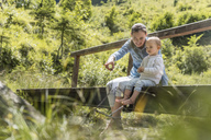 Mother and daughter sitting on wooden bridge - DIGF04727