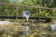 Mother and daughter sitting on wooden bridge, mountain stream - DIGF04730