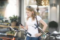 Germany, young woman with smartphone renting a city bike - SGF02200