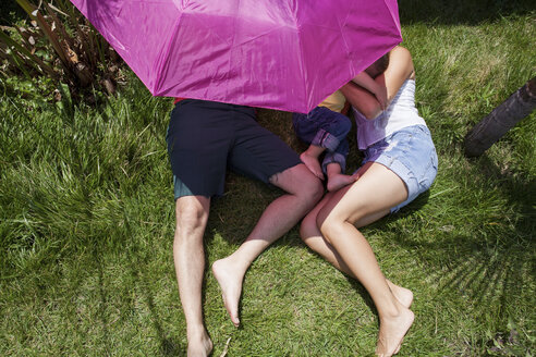Parents and son lying on grass under pink umbrella - CUF43766