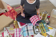 Woman sitting on floor with box of fabric samples - CUF43787